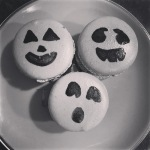 macarons with pumpkin faces painted on them.